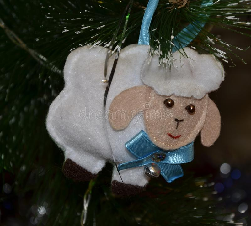 Christmas toys hanging on the tree.White lamb handmade with a blue bow on the neck with long ears. Close up. stock image