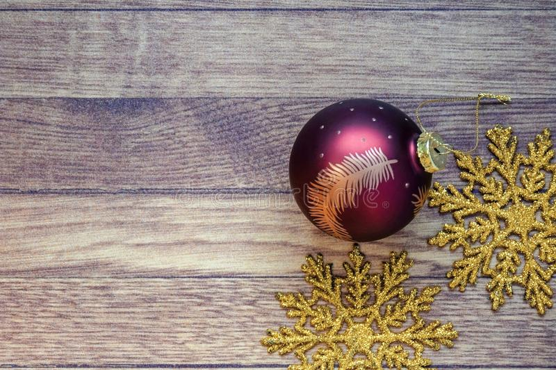 Christmas toys: one red christmas ball and two golden snowflakes on brown wooden background. New Year concept, composition. Retro royalty free stock photo
