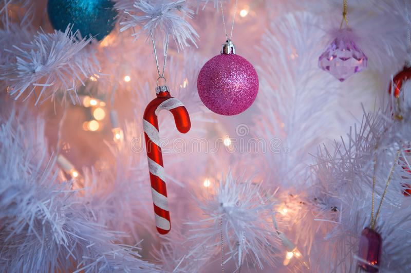 Christmas toys on a white artificial Christmas tree in a gentle style and gold lights garlands. Striped candy cane, pink and blue balls close-up stock photography
