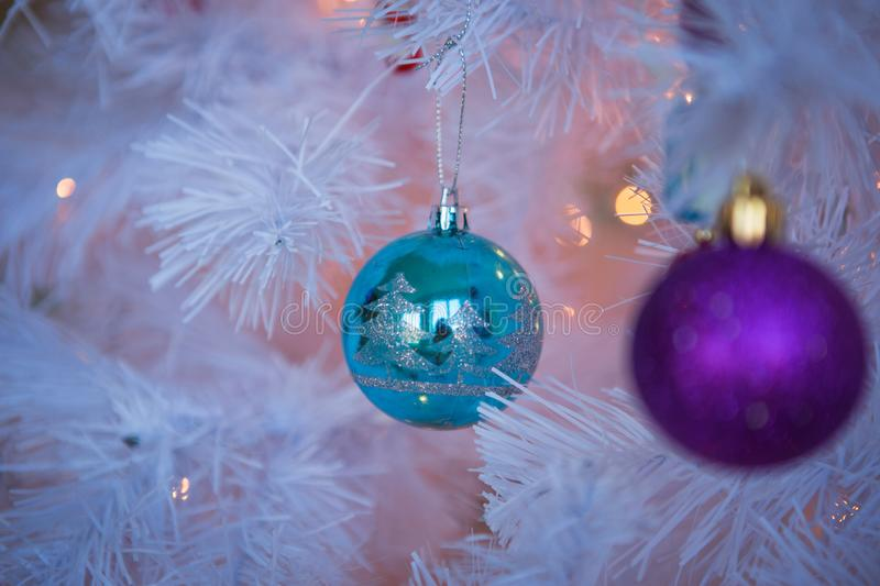 Christmas toys on a white artificial Christmas tree in a gentle style and gold lights garlands. Striped candy cane, pink and blue balls close-up royalty free stock image