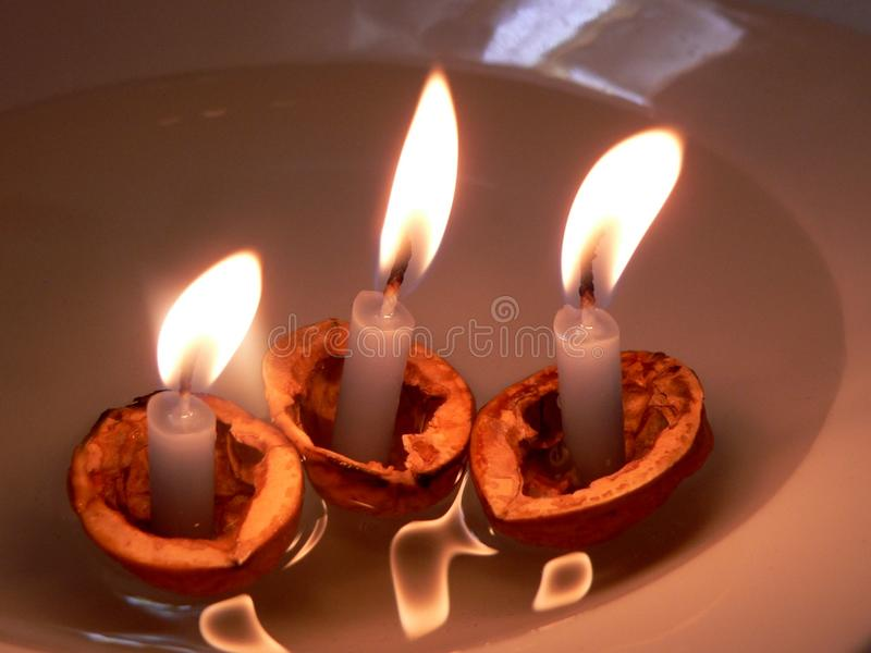 Christmas traditions boating. In Czech Republic.Shelled walnut and lighted candles floating in water stock images