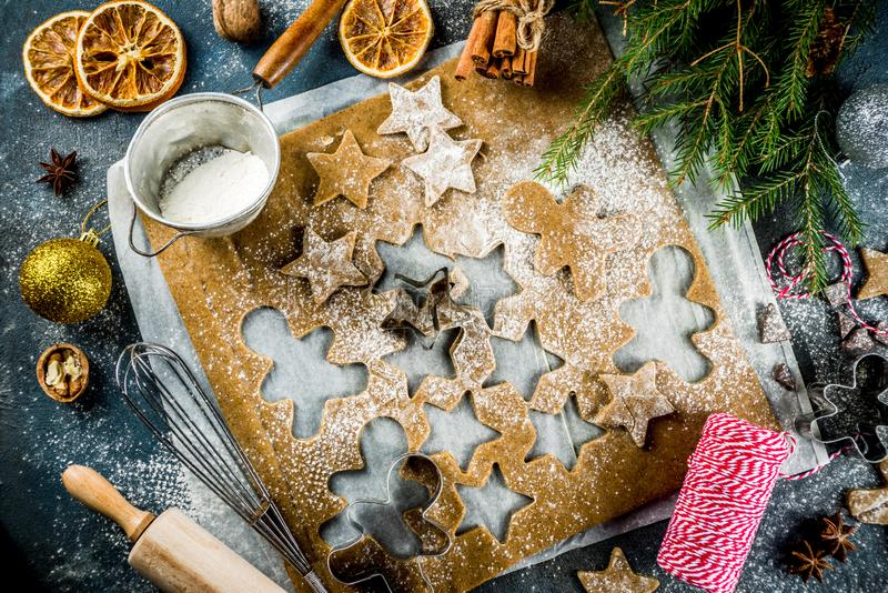 Making gingerbread cookie. Christmas traditions homemade baking Cooking gingerbread star cookies, gingerbread men, flat lay, top view, with accessories royalty free stock image
