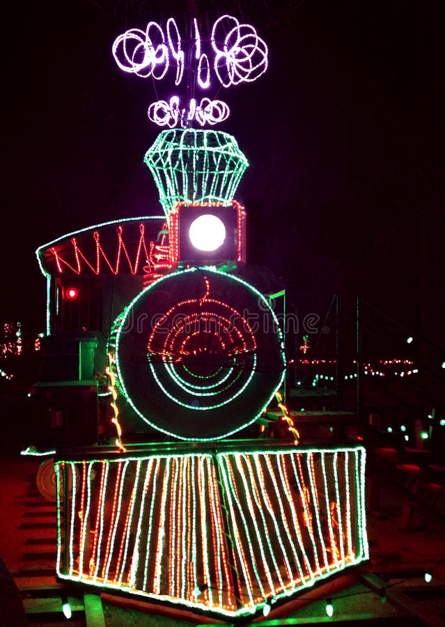 Christmas train with bright lights. Christmas train lined with brightly colored lights against black night background royalty free stock photography