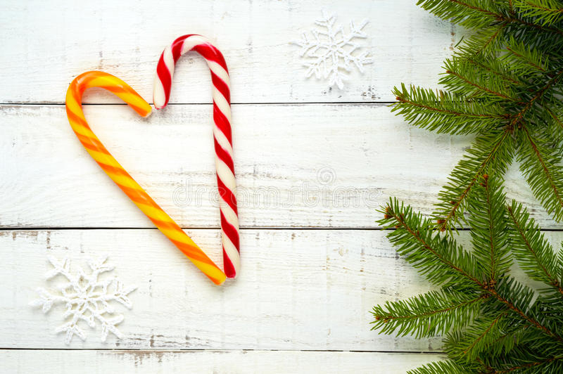 Christmas treats: bright candy canes, in a heart shape and green spruce branches on white a wooden board. stock images