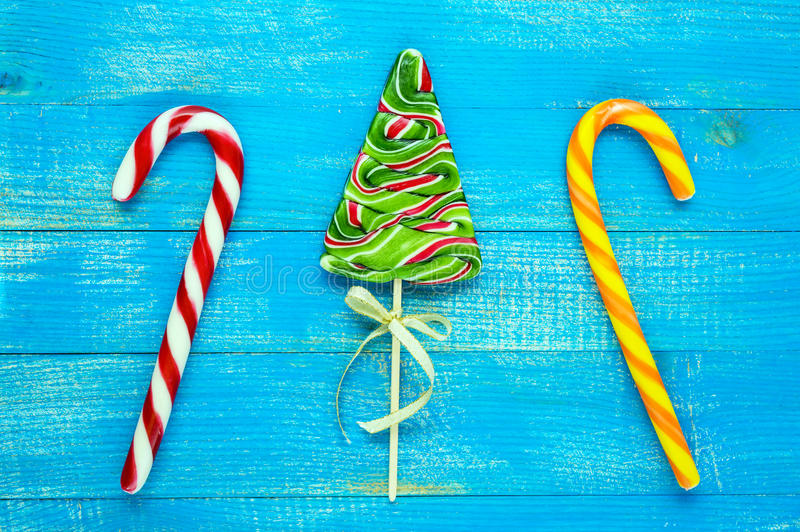 Christmas treats: colorful lollipops in the form of spruce, candy canes on a blue wooden board . stock image