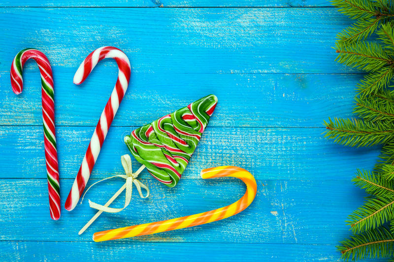 Christmas treats: colorful lollipops in the form of spruce, candy canes and green spruce branches on a blue wooden board . stock photo