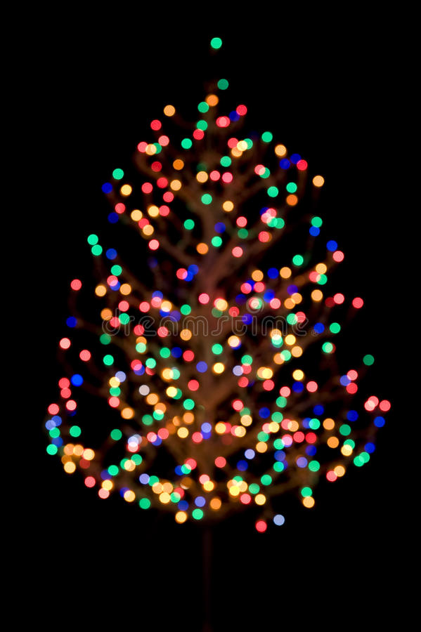 Vertical Shot Of A Christmas Tree With Lights Out Focus As An Abstract Picture On Black Background