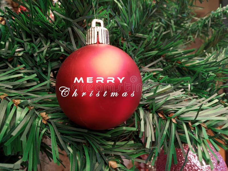 Christmas tree ornament & decoration closeup. Preparing & decorating Christmas tree with Merry Christmas text on red Xmas ball stock image