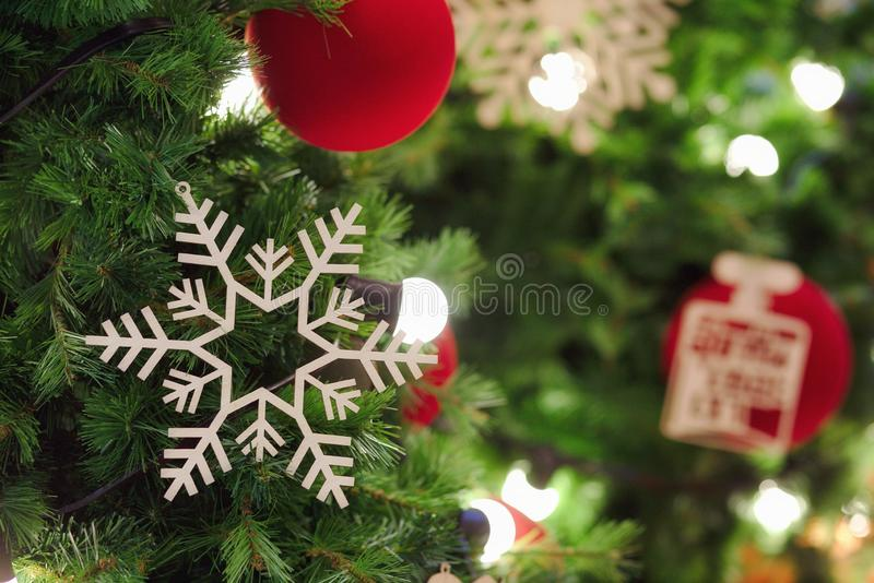 Snowflake and red ball hanging on Christmas tree with light up. Christmas, tree, background, new, decoration, holiday, red, xmas, design, blurred, celebration stock images