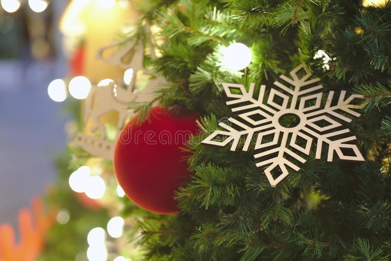 Snowflake and red ball hanging on Christmas tree with light up. Christmas, tree, background, new, decoration, holiday, red, xmas, design, blurred, celebration stock photo