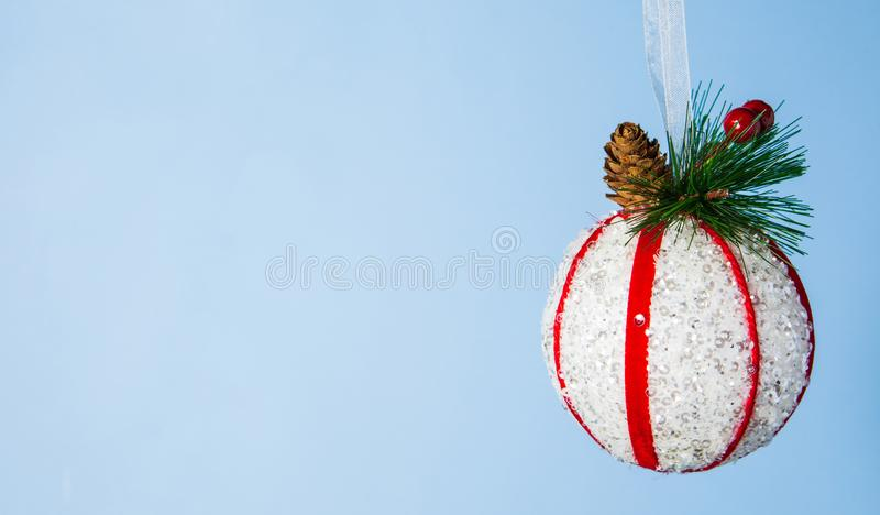 Christmas tree ball and spruce on light blue background, close-up stock photos