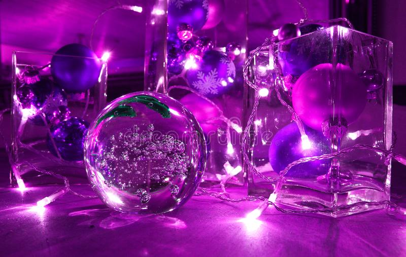 Christmas tree balls and jewellery with candle-lighted rally, in trend colour Ultra violet. Christmas tree balls and jewellery with candle-lighted rally, in the royalty free stock image