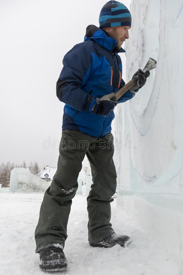 Portrait of a sculptor with a chisel in his hands. Christmas tree from a block of ice with a chisel stock image