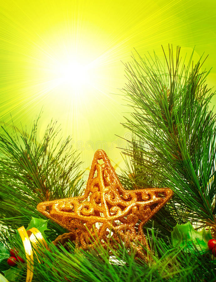 Christmas tree border. Picture of Christmastime decorative border, branch of Christmas tree decorated with golden star and ribbon, green pine tree twig on yellow royalty free stock photo