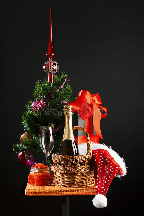 The Christmas tree, bottle of wine, bank with red caviar and New Year`s attributes. The decorated Christmas tree, bottle of wine, bank with red caviar and New stock photos