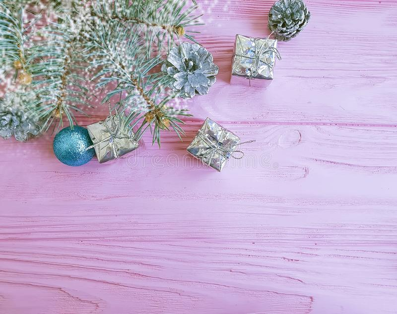 Christmas tree branch, ball, winter creative gift box ornament on a pink wooden background composition royalty free stock photos