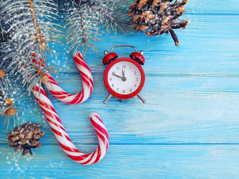 Christmas tree branch, candy alarm clock holiday on a blue wooden background stock image