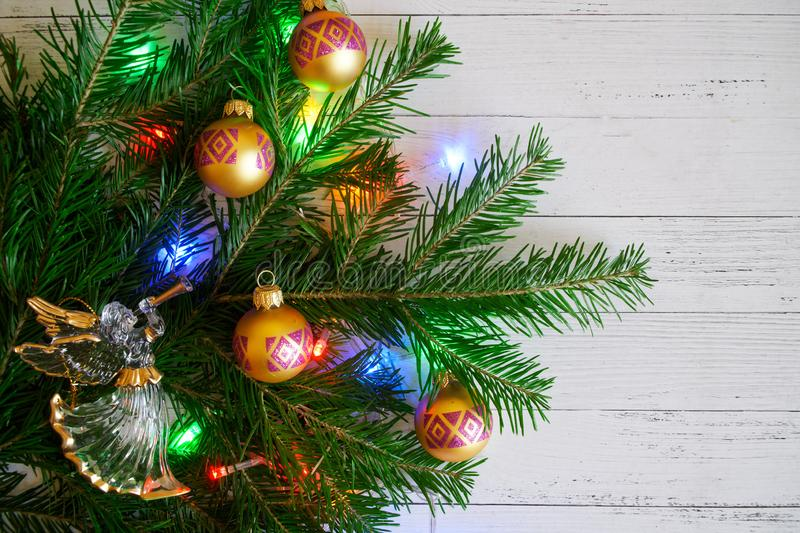 A Christmas tree branch decorated with toys and lights next to a stock photos