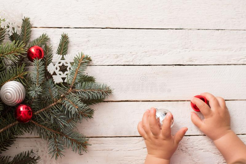 Christmas tree branch with decoration and baby hands on white wood background, copy space. winter new year card stock images