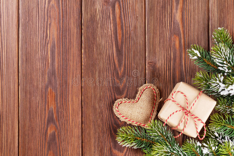 Christmas tree branch with gift box and heart toy. Christmas tree branch with snow, gift box and heart toy on wooden table. View with copy space royalty free stock photo
