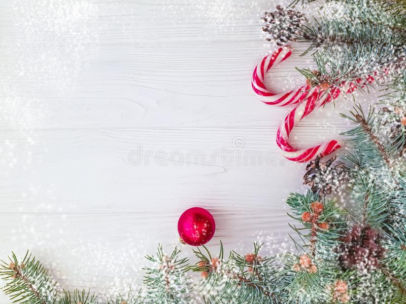 Christmas tree branch, winter , festive greeting snow candy on a white wooden background card ball. Christmas tree branch, pinecone, candy on a white wooden royalty free stock photo