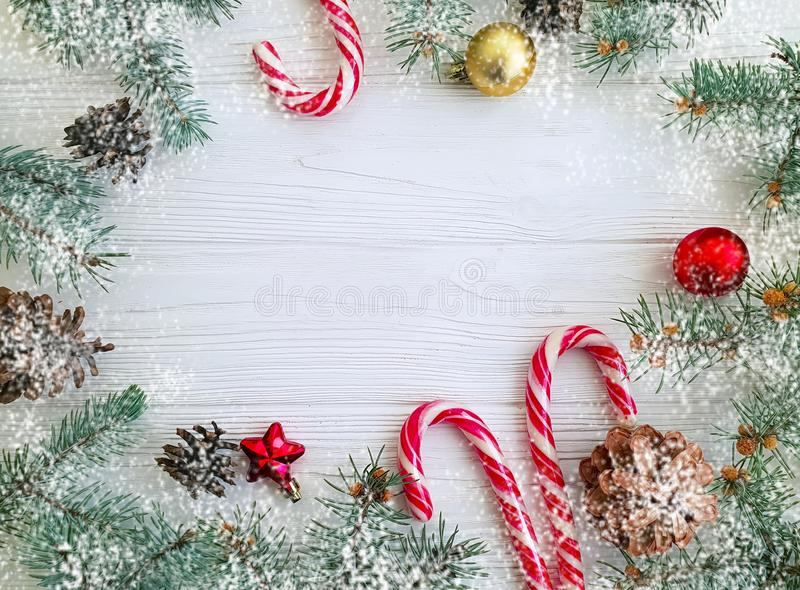 Christmas tree branch, pinecone, festive greeting snow candy on a white wooden background card ball. Christmas tree branch, pinecone, candy on a white wooden royalty free stock image