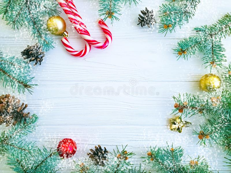 Christmas tree branch, pinecone, festive snow candy on a white wooden background card ball. Christmas tree branch, pinecone, candy on a white wooden frame snow royalty free stock image