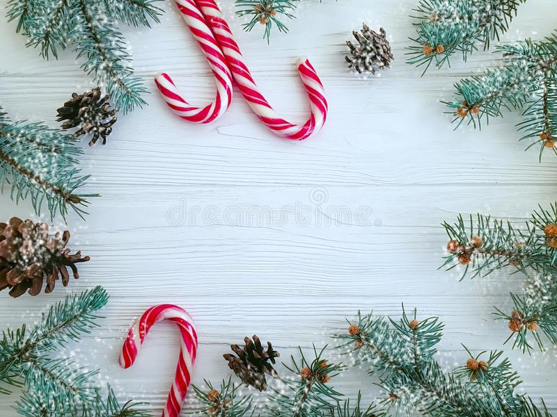 Christmas tree branch, pinecone, snow candy on a white wooden background. Christmas tree branch, pinecone, candy on a white wooden background frame snow stock photos