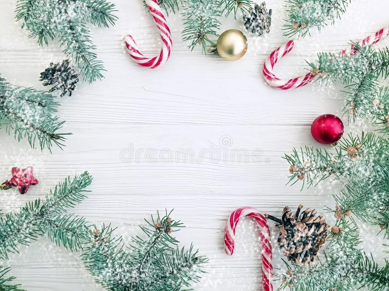 Christmas tree branch, pinecone winter , festive greeting snow candy on a white wooden background card ball. Christmas tree branch, pinecone, candy on a white stock images