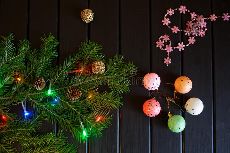 Christmas tree branch, snowflakes, cones, colorful lights and balls on a dark wooden background. Merry Christmas and Happy New Year - 2019 royalty free stock photo