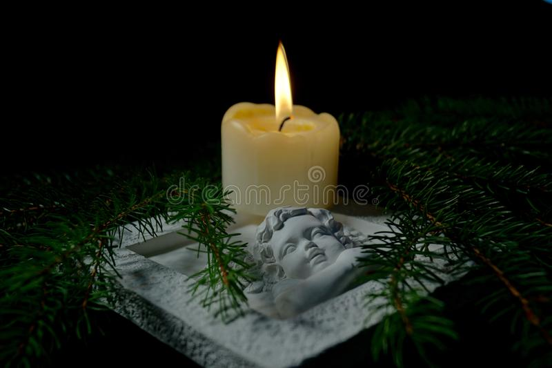 Christmas tree branches and an Angel lying on the table against darkness. Condolence card concept in christmas time or New year. Guardian angel, Fir branches stock images