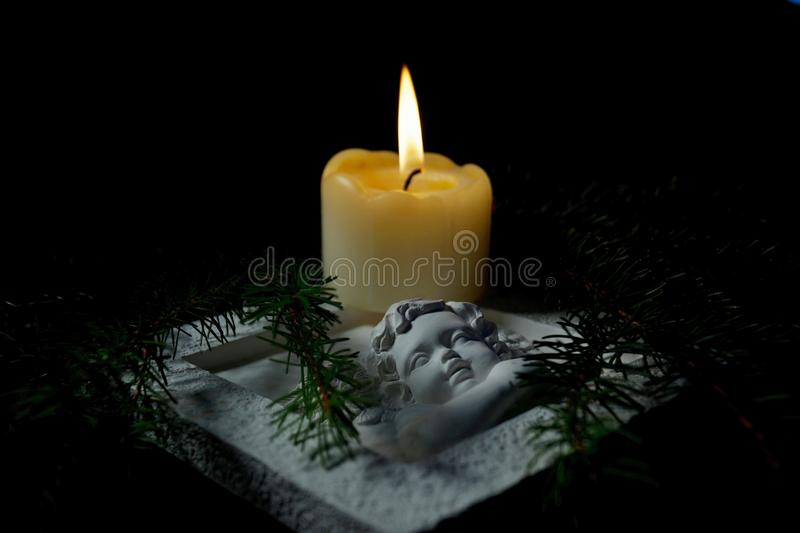 Guardian angel, Fir branches with a burning candle on black background. Condolence card concept in christmas time or New year. Christmas tree branches and an stock images