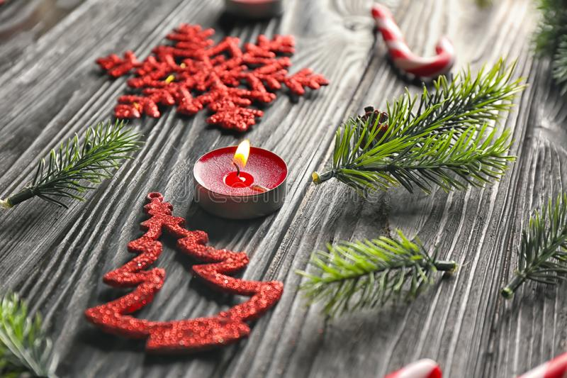 Christmas tree branches, burning candle and decorations on wooden background stock photography