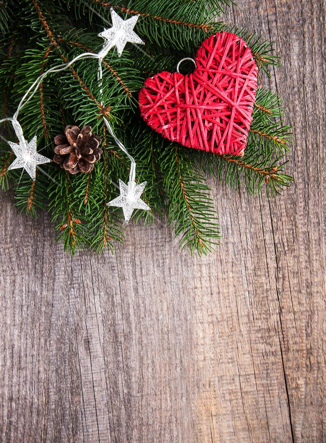 Christmas tree branches with heart decoration. On a wooden background stock image