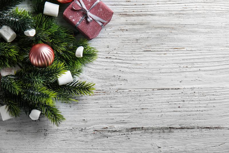 Christmas tree branches and tasty marshmallow on wooden table stock images