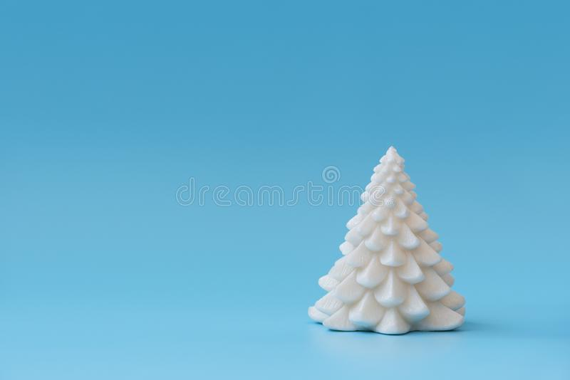 Christmas tree candle  on blue background. Christmas or New Year celebration concept. Copy space royalty free stock photography