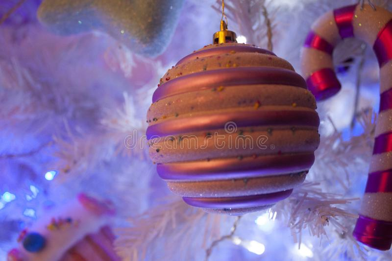 Christmas Tree Candy Ball Ornament. Christmas white tree with candy ornaments and white, blue, purple lights. Ball with sugar topping, white branched background stock photo