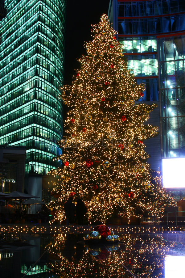 Christmas Tree in City Center. Brightly illuminated, tall Christmas tree in an large city with skyscraper buildings in the background stock photography