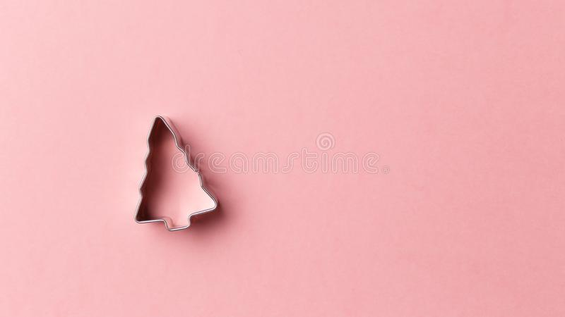 Christmas tree cookie cutter on pink background with copy space. Top view. Flat lay. Trendy colorful photo stock image