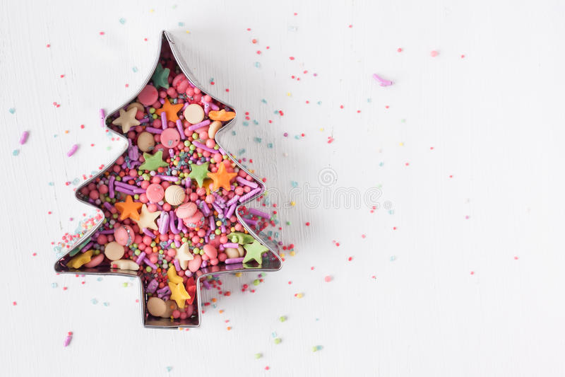 Christmas tree cookie cutter with sugar sprinkles stock photo