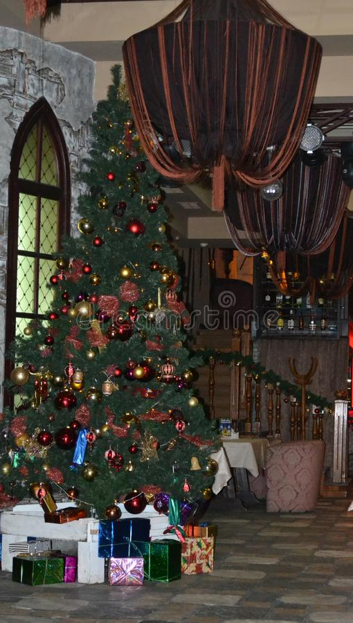 Christmas tree in a cozy cafe hall_. Beautiful Christmas tree with bright decorations and gifts in a cozy cafe hall stock photo