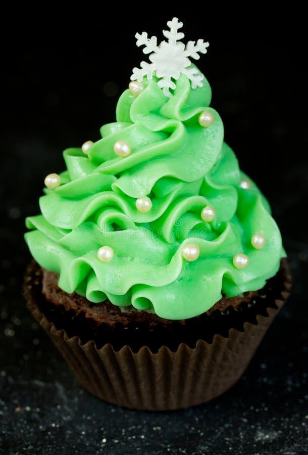 Christmas tree cupcake with green cream frosting. Beautiful chocolate cake shaped fairy Christmas tree royalty free stock photo