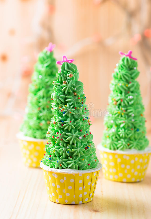 Christmas tree cupcake. On wood background royalty free stock image