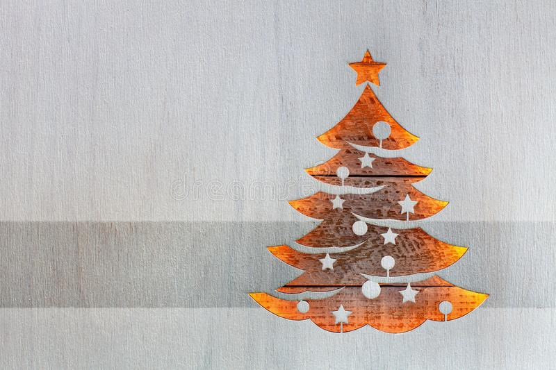 Christmas tree shape in wooden board letting through warm lights. Christmas tree cut out from white painted wooden board letting warm ligths shine through royalty free illustration
