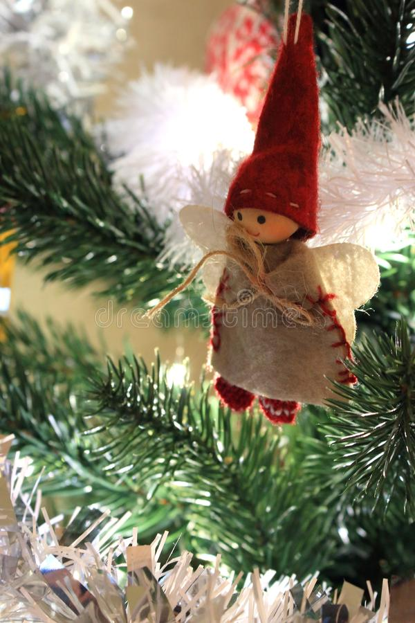 Christmas tree with cute angel in red santa hat. Christmas tree with smiling angel boy figure and white garland. stock photo