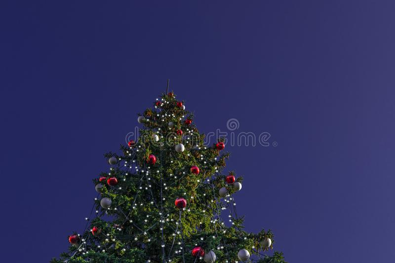 Christmas tree decorated with electric garlands and colorful balls on a blue-violet night background stock photo