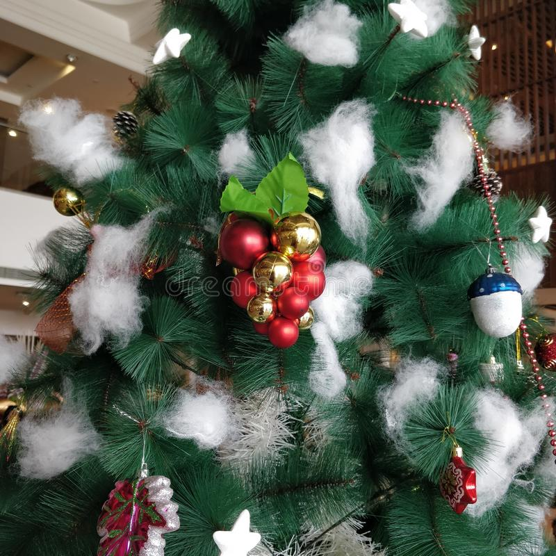 Christmas tree is decorated with golden bell, santa claus, pine cones, lights,snow man etc. Christmas tree is decorated with golden bell, santa claus, pine royalty free stock images