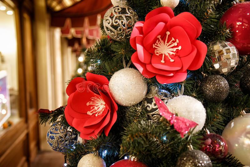 Christmas tree decorated with red flowers and Christmas balls. Christmas decorations. New Year decoration Christmas tree stock images