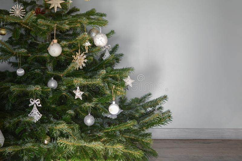 Christmas tree decorated with toys near a gray wall. Christmas tree decorated with toys against a gray wall royalty free stock image