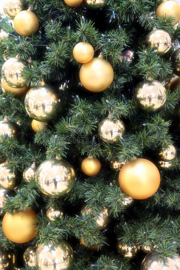 Christmas tree decoration in gold and silver tones on a green tree stock images